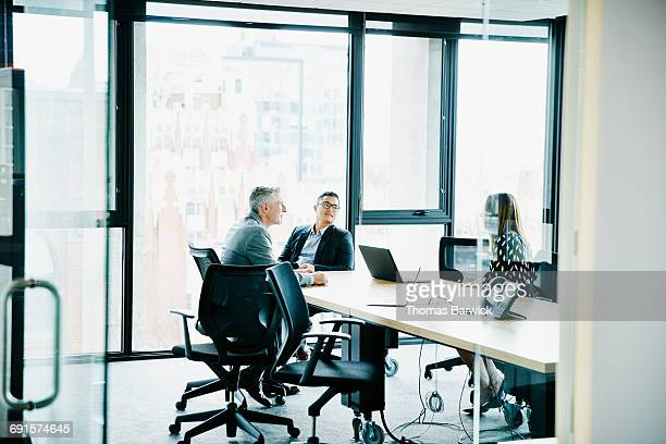 Colleagues in discussion in office conference room