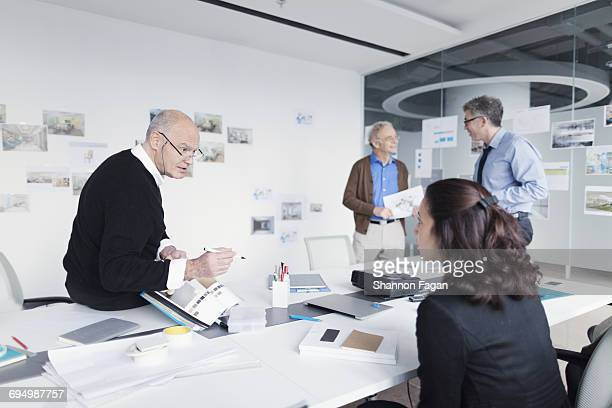 Colleagues in meeting talking about design layouts