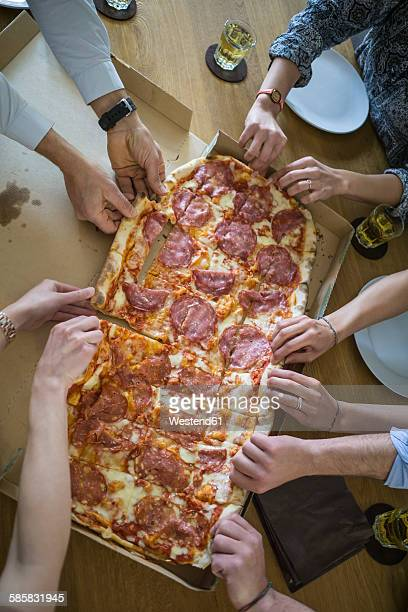 Colleagues in office sharing pizza
