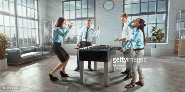 Collègues au bureau jouent jeu de table football/kicker. Une seule équipe émotionnellement réjouit victoire