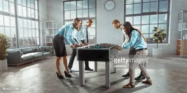 Collègues au bureau jeu table football/kicker