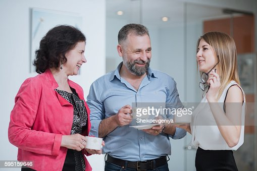 colleagues in the office talking during the coffee break : Stock Photo