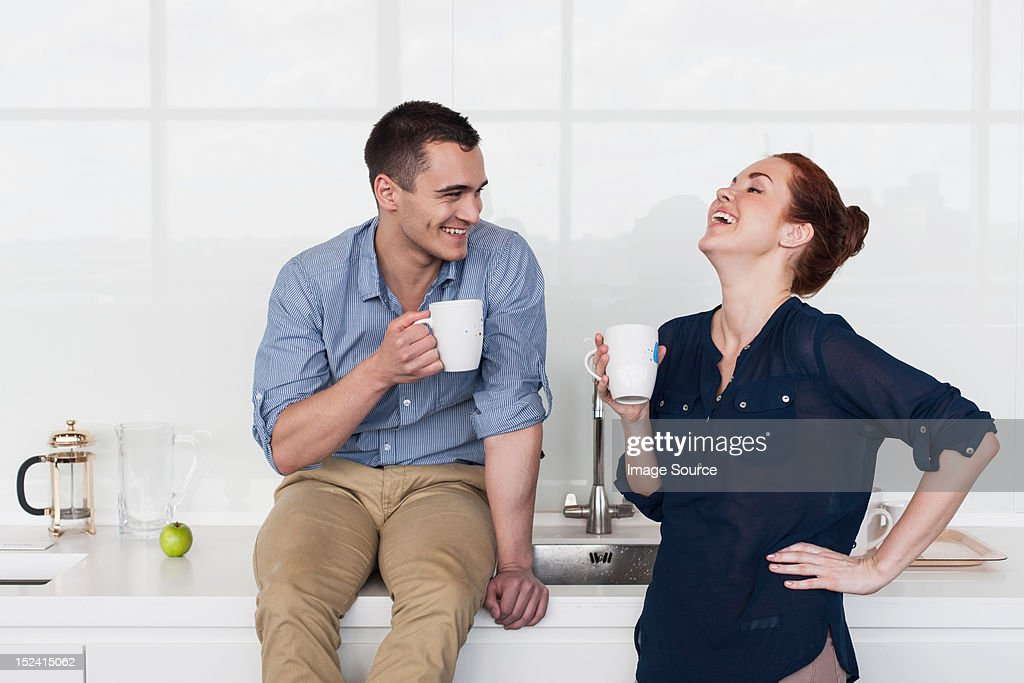 Colleagues laughing in kitchen : Stock Photo