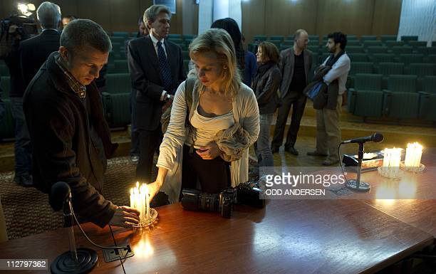 Colleagues light candles at the end of a memorial service for slain photojournalists Tim Hetherington and Chris Hondros in Benghazi on April 21 2011...