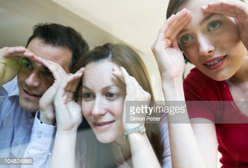 3 colleagues look thru glass : Stock Photo
