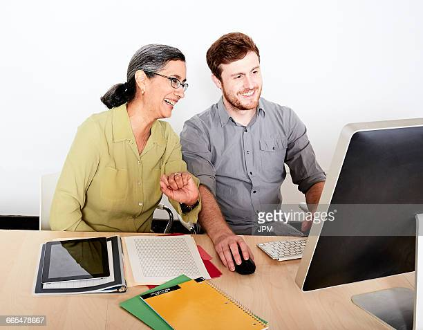 Colleagues looking at computer monitor smiling