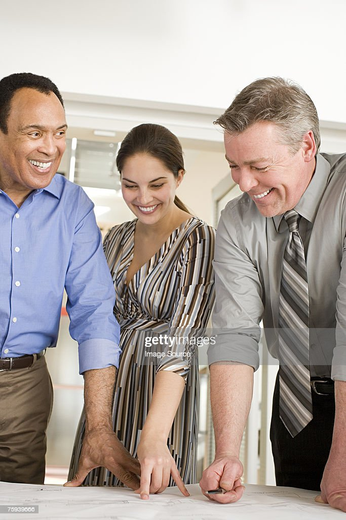 Colleagues looking at plans and smiling : Stock Photo