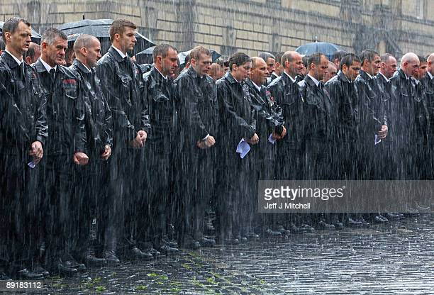 Colleagues of firefighter Ewan Williamson gather in torrential rain outside St Giles Cathedral on July 22 2009 in Edinburgh Scotland Firefighters...