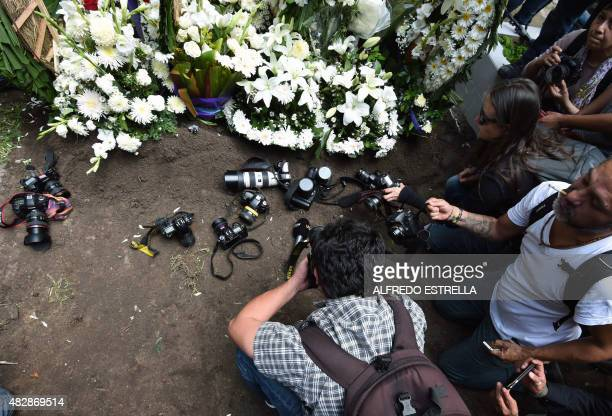 Colleagues of murdered Mexican photographer Ruben Espinosa place their cameras beside his grave during his burial at the Dolores cemetery in Mexico...