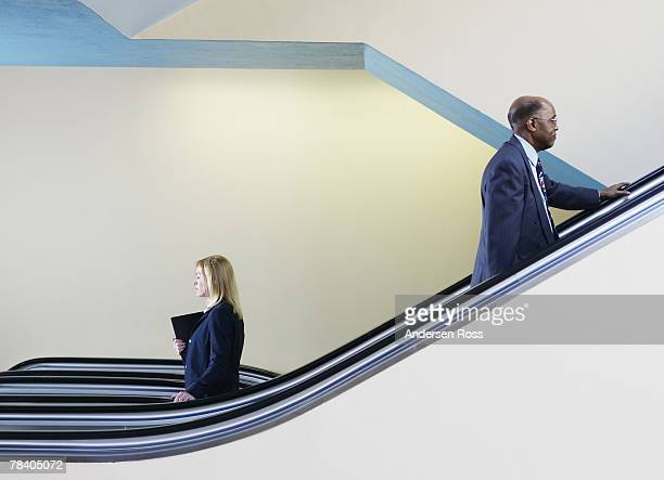 Colleagues passing on escalator