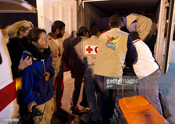 Colleagues react as the bodies of photojournalists Tim Hetherington and Chris Hondros are loaded into a refrigerated truck for repatriation by an...