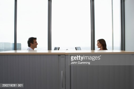 Colleagues seated at opposite desks in office, side view : Stock Photo