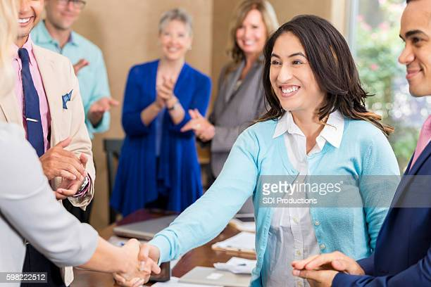 Colleagues shake businesswoman's hand after concluding successful deal