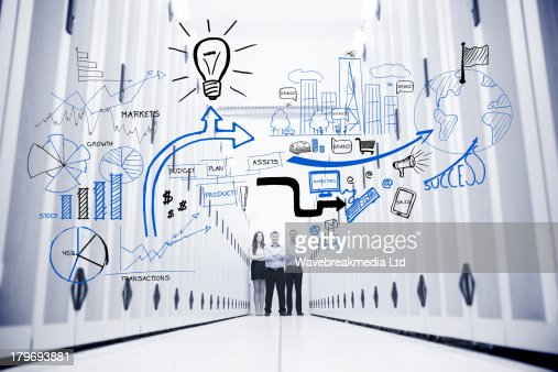 Colleagues standing in a data center in front of drawings : Stock Photo