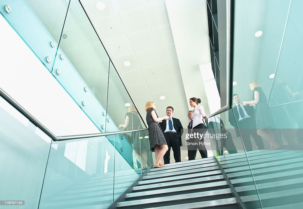 Colleagues standing on staircase in office building : Stock Photo