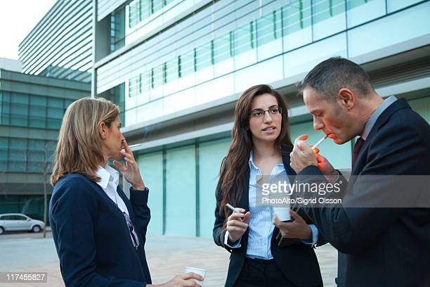 Colleagues taking smoke break outdoors