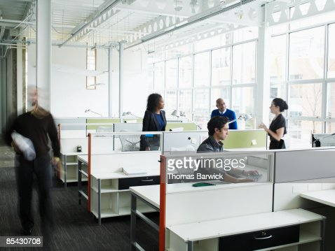 Colleagues talking at workstations : Stock Photo