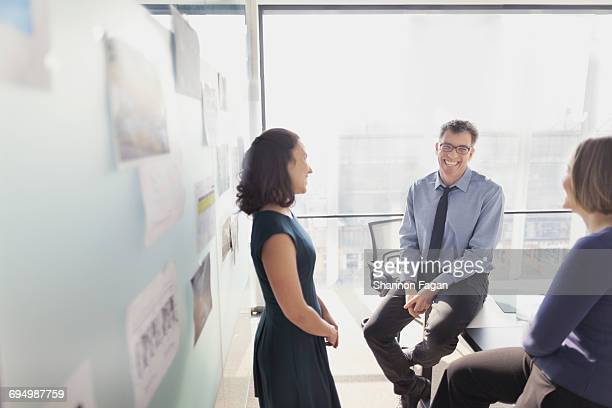 Colleagues talking in conference room together