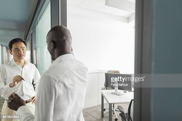 Colleagues talking in office hallway
