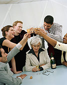 Colleagues toasting champagne glasses above businesswoman's head