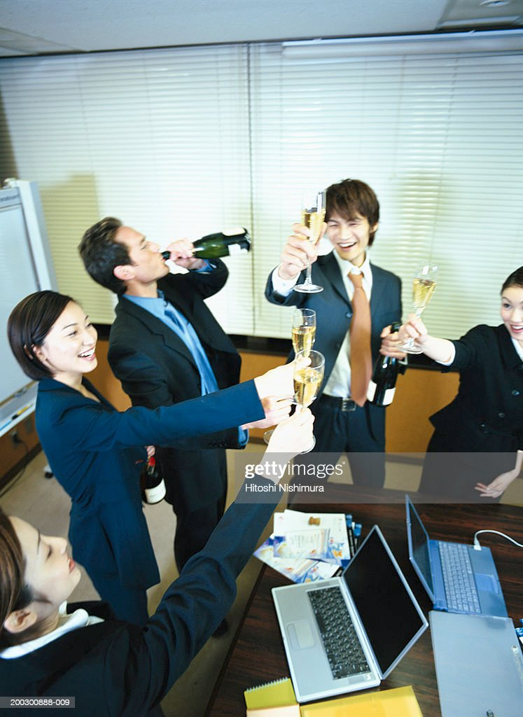 Colleagues toasting in office, elevated view : Stock Photo