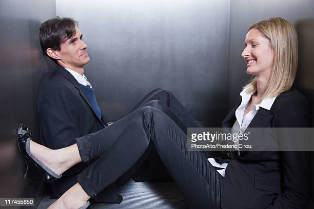 Colleagues trapped in elevator, sitting on floor chatting