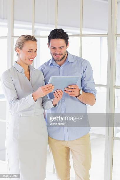 Colleagues using digital tablet in the office
