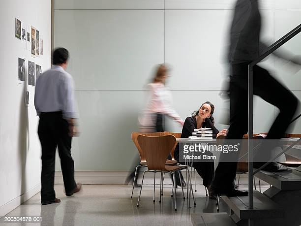 Colleagues walking in board room, woman sitting at conference table