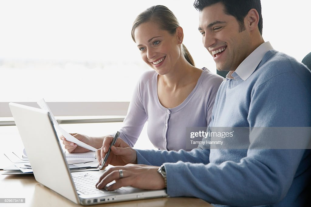 Colleagues working on laptop together : Foto stock