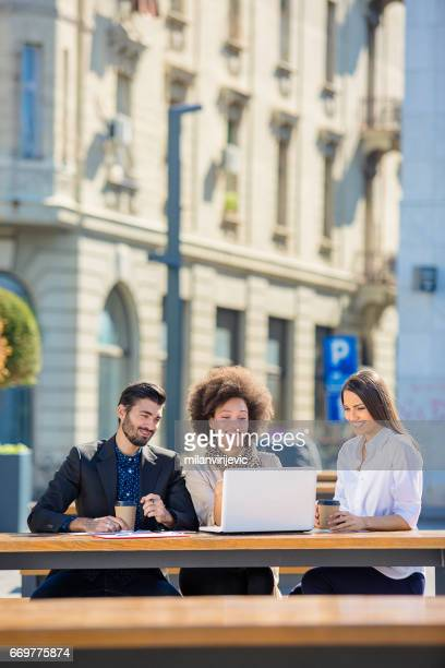 Colleagues working outdoors at computer
