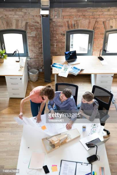 Colleagues working together on plan in modern office