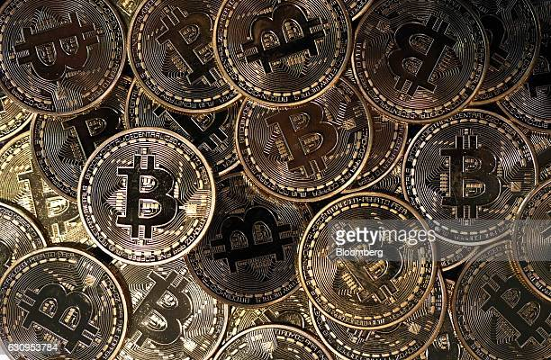 A collection of bitcoin tokens sit in this arranged photograph in London UK on Wednesday Jan 4 2017 The electronic coin that trades and is regulated...