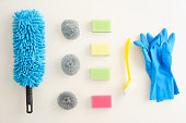 Collection of pastel-coloured cleaning supplies on white background