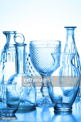 Collection of glass vases backlit with blue tone.