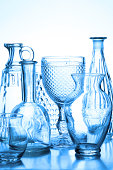 A studio shot of a collection of glass vases, wine glasses and glass bottles back lit toned in blue color in a reflective surface. Glasses features a variation of finished surfaces like bubbles, ruffl