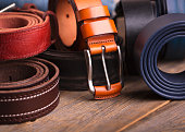 Leather colored belts on a wooden table
