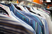 Hangers with colorful male shirts in fashion mall, close up. Shallow depth of field, focus on striped garment