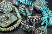 Vintage Native American Turquoise and Sterling Silver Jewelry, Necklaces, Bracelets and Concho on a black background.