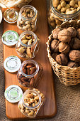 Assortment of mixed nuts and wicker basket on sack background