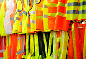 Collection of security reflective cloths, orange and yellow, hanging in row vests.