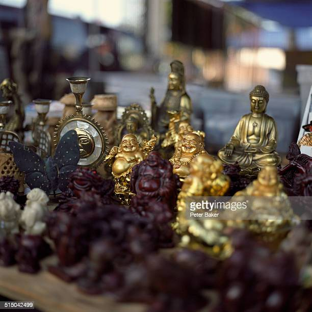 A collection of various Buddha statues for sale at a flea market