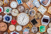 Collection of vintage rusty watches and parts on a brown old rusted background