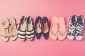 Collection of women's shoes on pink background. Top view