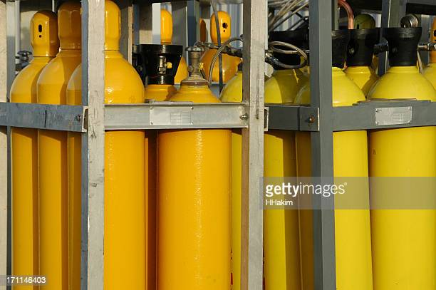 A collection of yellow gas tanks in cages