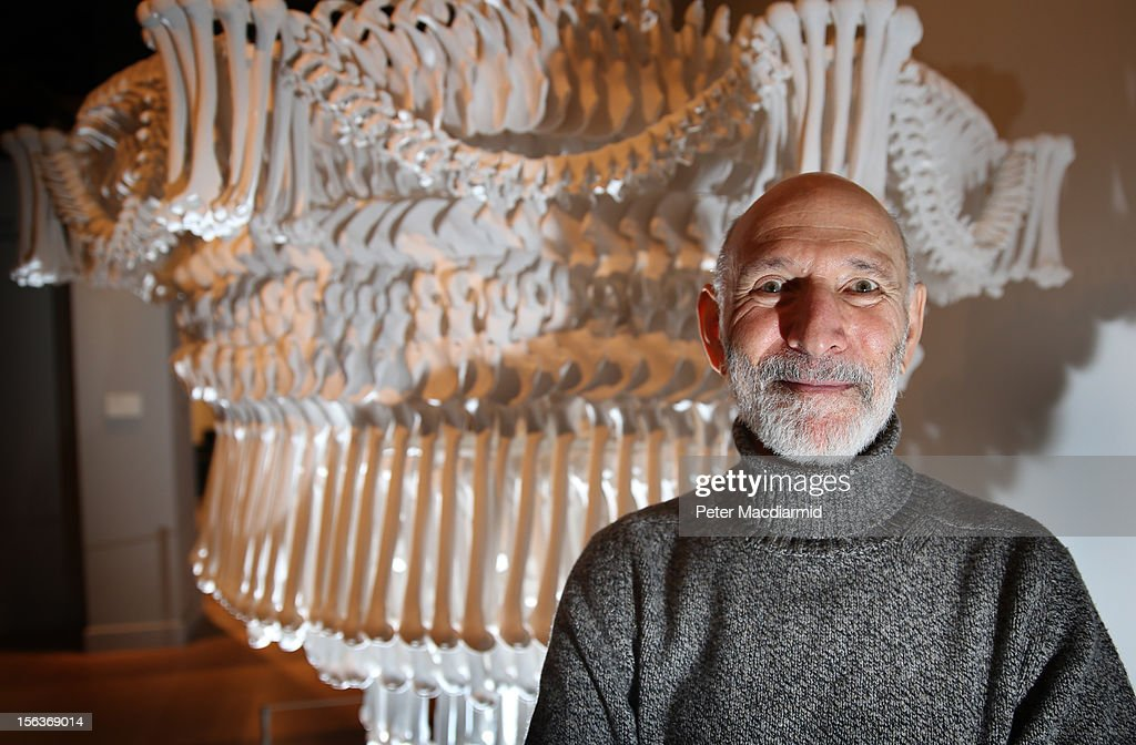 Collection owner Richard Harris stands in front of a chandelier made from plaster casts of bones by artist Jodie Carey at the 'Death: A Self-portrait' exhibition at the Wellcome Collection on November 14, 2012 in London, England. The exhibition showcases 300 works from a unique collection by Richard Harris, a former antique print dealer from Chicago, devoted to the iconography of death. The display highlights art works, historical artifacts, anatomical illustrations and ephemera from around the world and opens on November 15, 2012 until February 24, 2013.