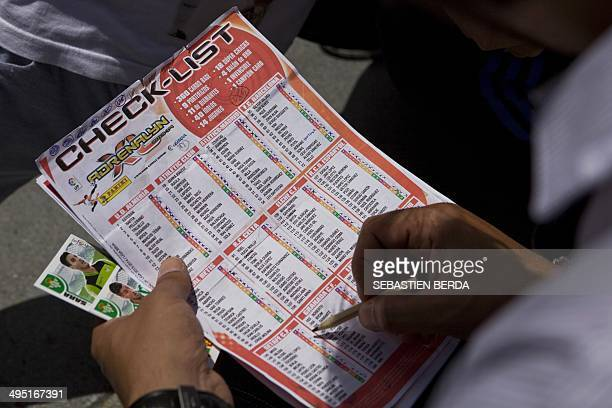 A collector checks his list of sticker duplicates of the Spanish League 2014's football players near the flea market in Madrid on June 1 2014 AFP...