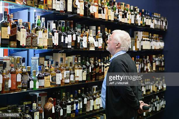 A collector views whiskies going on sale today at McTears Auctioneers on September 4 2013 in GlasgowScotland Whiskey collectors as far afield as the...