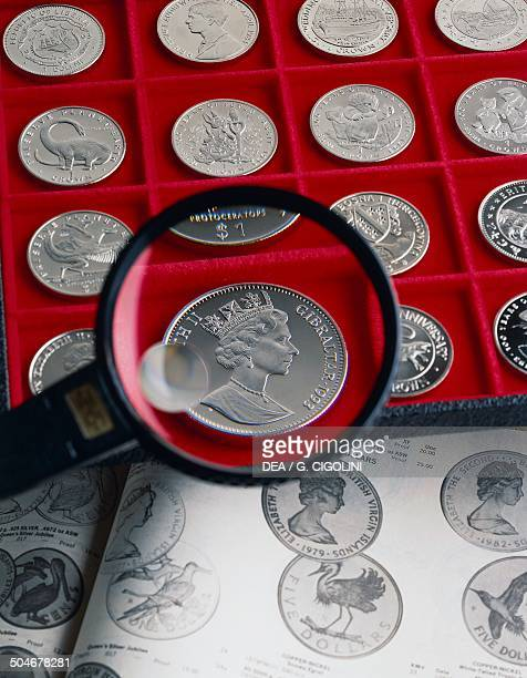 Collectors coins and a magnifying glass and catalogue