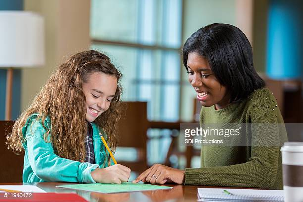 College age tutor helping elementary age girl with homework