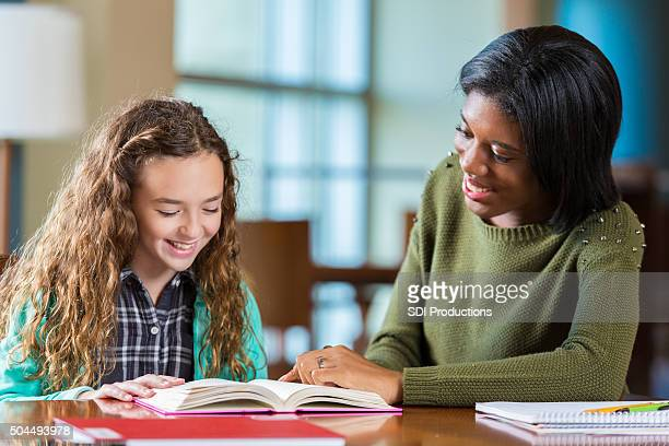 College age tutor helping elementary school student with homework